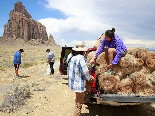 Kyle Jim, center, and Shaneyka Yazzie of the Shiprock AmeriCorps group get ready to ride on the back of a truck carrying materials to be used for a control erosion project on Friday at the Shiprock pinnacle. In back Kendrick Joey, left, and Alejandro Cota scrutinize a sodden trail before heading out.