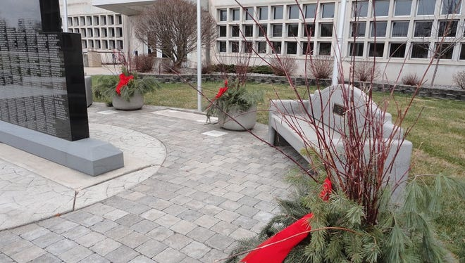 An anonymous person decorated the Wood County Veterans Memorial with pine boughs and red ribbons for the holiday. The decorations made it festive and inviting for visitors, especially since there was no snow on the ground.