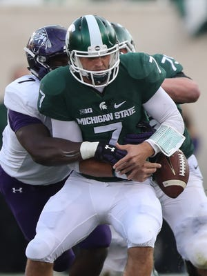 Michigan State Spartans Tyler O'Connor is forced to fumble by the Northwestern Wildcats Ifeadi Odenigbo during second half action Saturday, October 15, 2016 at  Spartan Stadium in East Lansing MI.  Kirthmon F. Dozier/Detroit Free Press