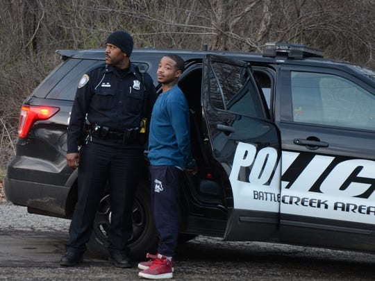Battle Creek Police Officer Justin Broughton stands with a Kalamazoo man suspected of running from police after a traffic stop Tuesday.