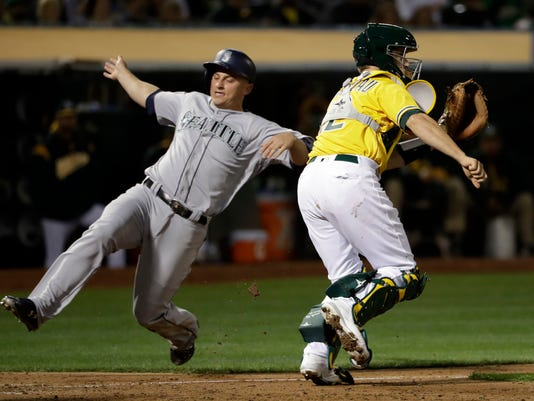 Seattle Mariners' Kyle Seager, left, scores past Oakland Athletics catcher Dustin Garneau after a double from Ben Gamel during the sixth inning of a baseball game Tuesday, Aug. 8, 2017, in Oakland, Calif. (AP Photo/Marcio Jose Sanchez)