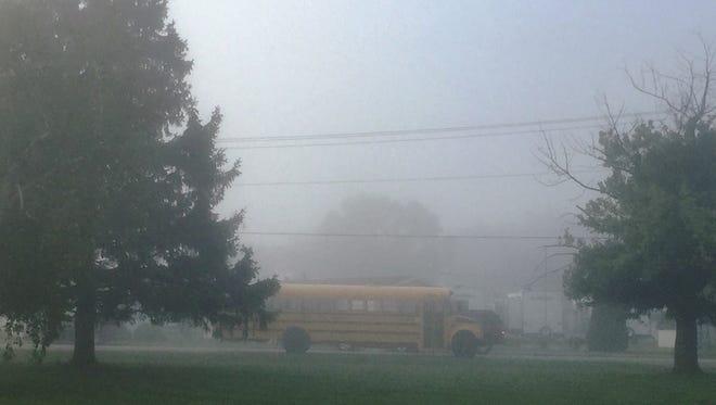 A Fremont school bus rolls along a foggy Cedar Street this morning.