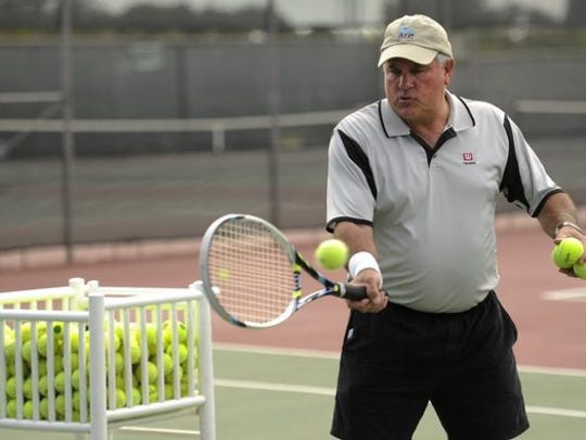 Rick Meyers hits tennis balls during a tennis lesson in October 2014 at Rose Park Tennis Center.