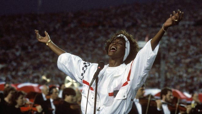 TAMPA, FL - JANUARY 27:  Whitney Houston sings the National Anthem before a game with the New York Giants taking on the Buffalo Bills prior to Super Bowl XXV at Tampa Stadium on January 27, 1991 in Tampa, Florida. The Giants won 20-19. (Photo by George Rose/Getty Images) [Via MerlinFTP Drop]