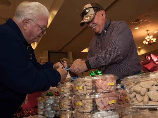 Co-Owner of Osito's Biscochitos Joe Porras, right, finalizes a sale with customer Richard Lillja, left.