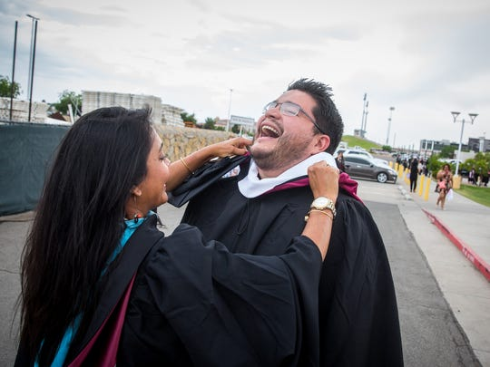 NMSU faculty member Moumita Choudhury, left, helps Communication Disorder Masters Student Daniel Soliz with his graduation robes before the start of commencement ceremonies at the Pan American Center, May 14, 2016.