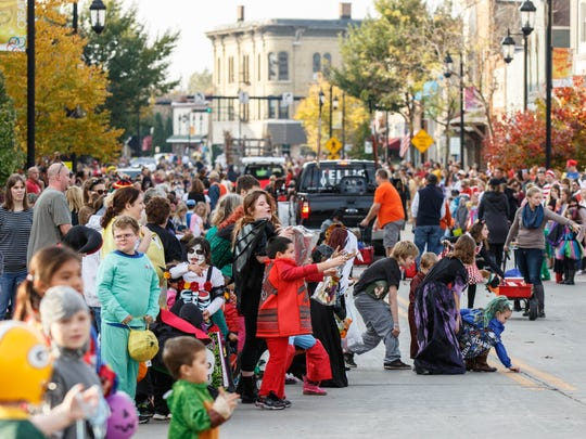 Children scramble for loose candy as the Oconomowoc Halloween Parade rumbles through town on Saturday, Oct. 29, 2016.