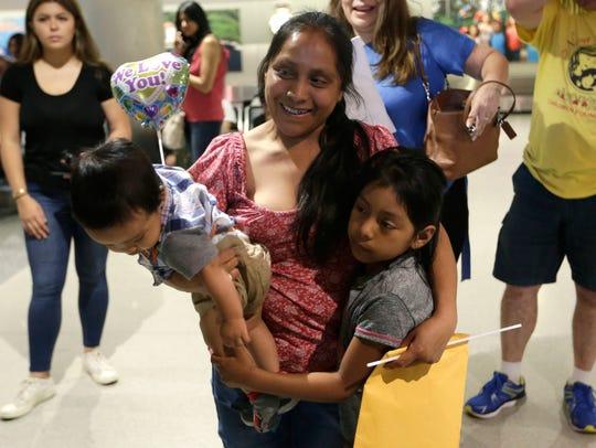 Buena Ventura Martin-Godinez, center, holds her son