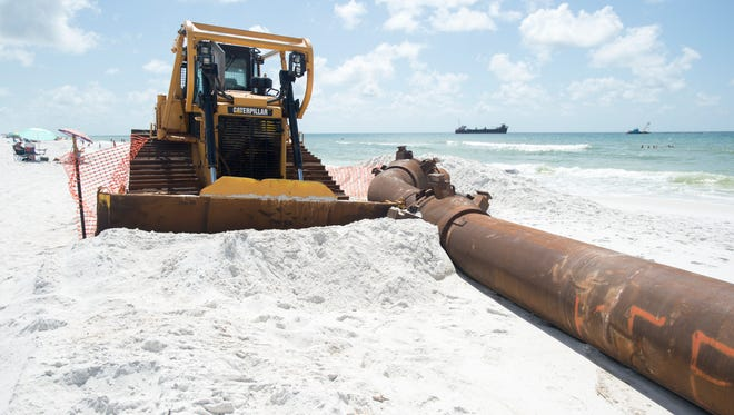 Beach-goers hit the beach July 28, 2016, as the Pensacola Beach renourishment project reaches its halfway point.