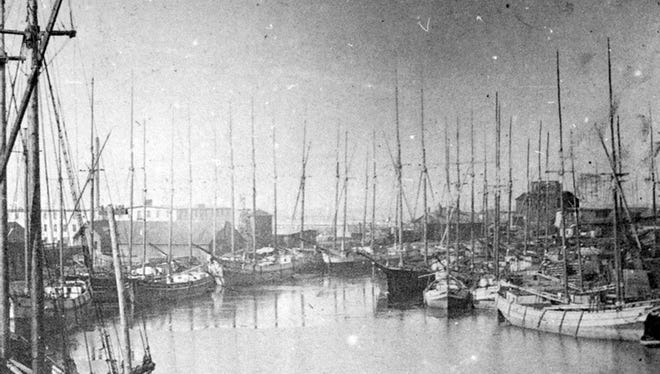 A common view for new immigrants arriving in Sheboygan.  Sixteen lumber boats, most owned by Sheboyganites, were tied up along the docks of the Sheboygan River east of the Eighth Street Bridge in this 1892 image. George Spratt's Furniture factory is seen behind the masts at right. The large white building in the rear is the Frost Veneer factory. It wasn't unusual to have a dozen more ships lying outside the harbor waiting for others to leave the docks.