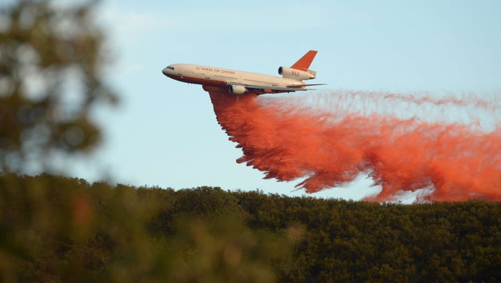 An air tanker drops fire retardant along a ridge to