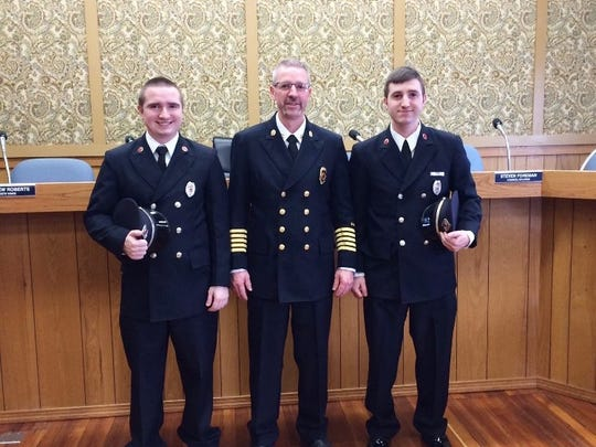 Eric Waltemire, center, with his son's Jacob and E.J. who are both firefighters, during Waltemire's pinning as Chief.