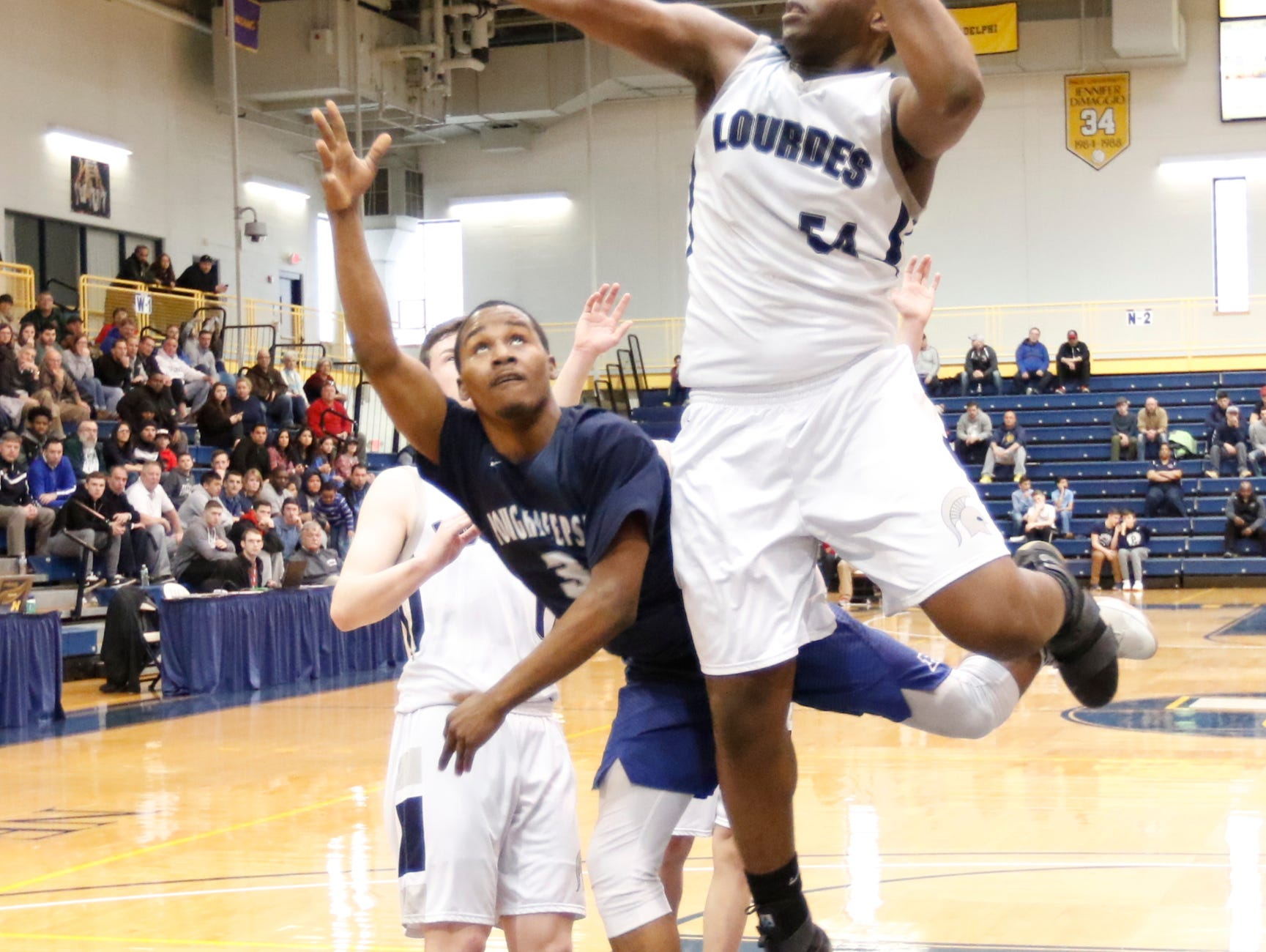 Our Lady of Lourdes' James Anozie (54) blocks a shot by Poughkeepsie's Mo'Quez Dickens (3) during the boys NYSPHSAA Class A regional final at Pace University's Goldstein Fitness Center in Pleasantville on Saturday, March 11, 2017.