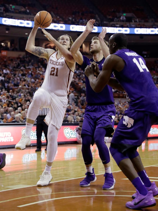 Texas forward Dylan Osetkowski (21) drives to the basket against Kansas State forwards Makol Mawien (14) and Dean Wade, center, during the second half of an NCAA college basketball game Wednesday, Feb. 7, 2018, in Austin, Texas. Kansas won 67-64. (AP Photo/Eric Gay)