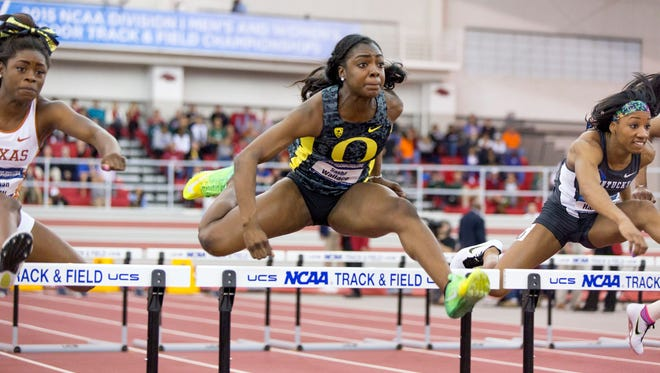 Oregon athlete Sasha Wallace, center, leaps over a hurdle during the 60-meter hurdles event during the NCAA indoors track and field national championships Friday, March 13, 2015, in Fayetteville, Ark.