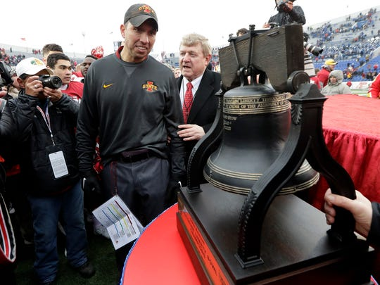 Iowa State head coach Matt Campbell is presented with his team's trophy after beating Memphis in the Liberty Bowl NCAA college football game, Saturday, Dec. 30, 2017, in Memphis, Tenn. Iowa State won 21-20. (AP Photo/Mark Humphrey)