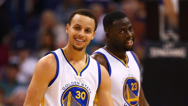 Mar 9, 2015; Phoenix, AZ, USA; Golden State Warriors guard Stephen Curry (30) and forward Draymond Green (23) smile as they react against the Phoenix Suns at US Airways Center. The Warriors defeated the Suns 98-80. Mandatory Credit: Mark J. Rebilas-USA TODAY Sports