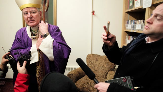 Archbishop John Nienstedt talks to the media at Our Lady of Grace Church in Edina, Minn. on Sunday, Dec. 15, 2013.