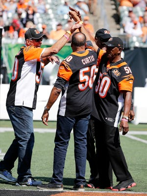 Former Bengals quarterback Ken Anderson, high-fives other former players Isaac Curtis and Lemar Parrish during halftime ceremonies in honor of the Bengals' 50th season at Paul Brown Stadium Sunday September 10, 2017.