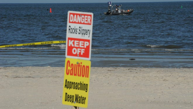 A Virginia Marine Resources Commission boat scans the water for the missing swimmer off Cape Charles Sunday. Cape Charles plans to install safety markers in the waters after the drowning of Alvaro Lopez of Tasley on Sunday.