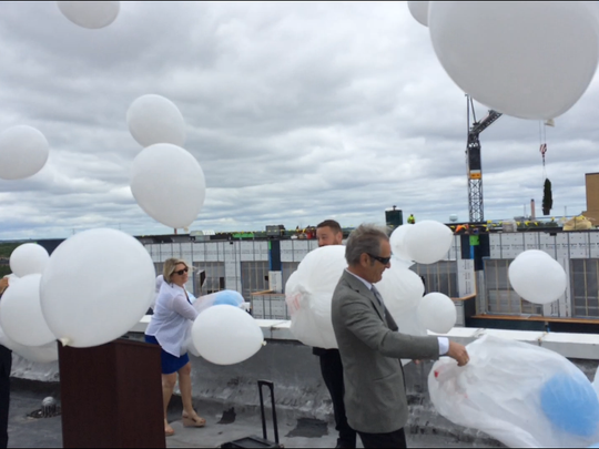 Max Dermond, in gray, of Dermond Property Investments, releases balloons to celebrate the topping off of the Metreau Apartments building.