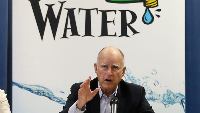 Gov. Jerry Brown talks with reporters after a meeting about the drought at his Capitol office in Sacramento.
