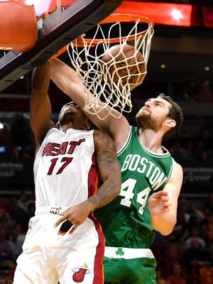 Miami Heat guard Rodney McGruder dunks the ball as Boston Celtics center Tyler Zeller applies pressure during the first half at American Airlines Arena.