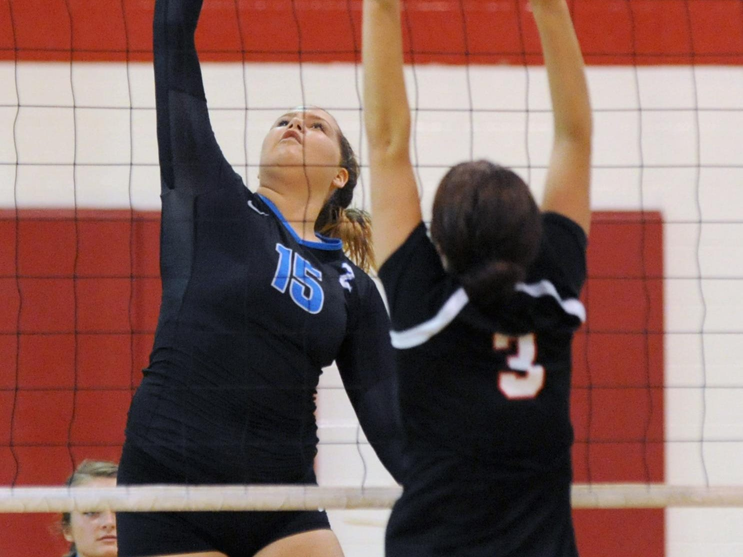 Zanesville's Desiree Blanton spikes the ball past Rosecrans' Emily Nash during a match Thursday at Bishop Rosecrans High School. Zanesville defeated Rosecrans in three sets.