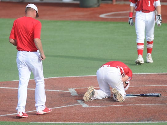 Albany's Brian Hamilton kneels at home plate after
