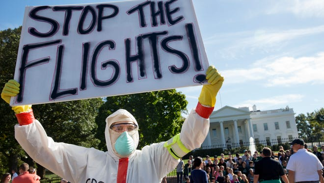 Jeff Hulbert, of Annapolis, Md., protests U.S. handling of Ebola cases outside of the White House Friday, Oct. 17, 2014, in Washington. The CDC and FAA are both against flight bans.