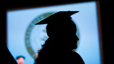 A member of the New England College of Business graduating class of 2014 stands during commencement exercises in Boston, Saturday, May 17, 2014.