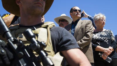 Darin Stanley (left) stands guard while Ariz. representatives David Livingston (center) and Judy Burges stand on stage during a news conference for Cliven Bundy in Bunkerville, Nevada, April 14, 2014.