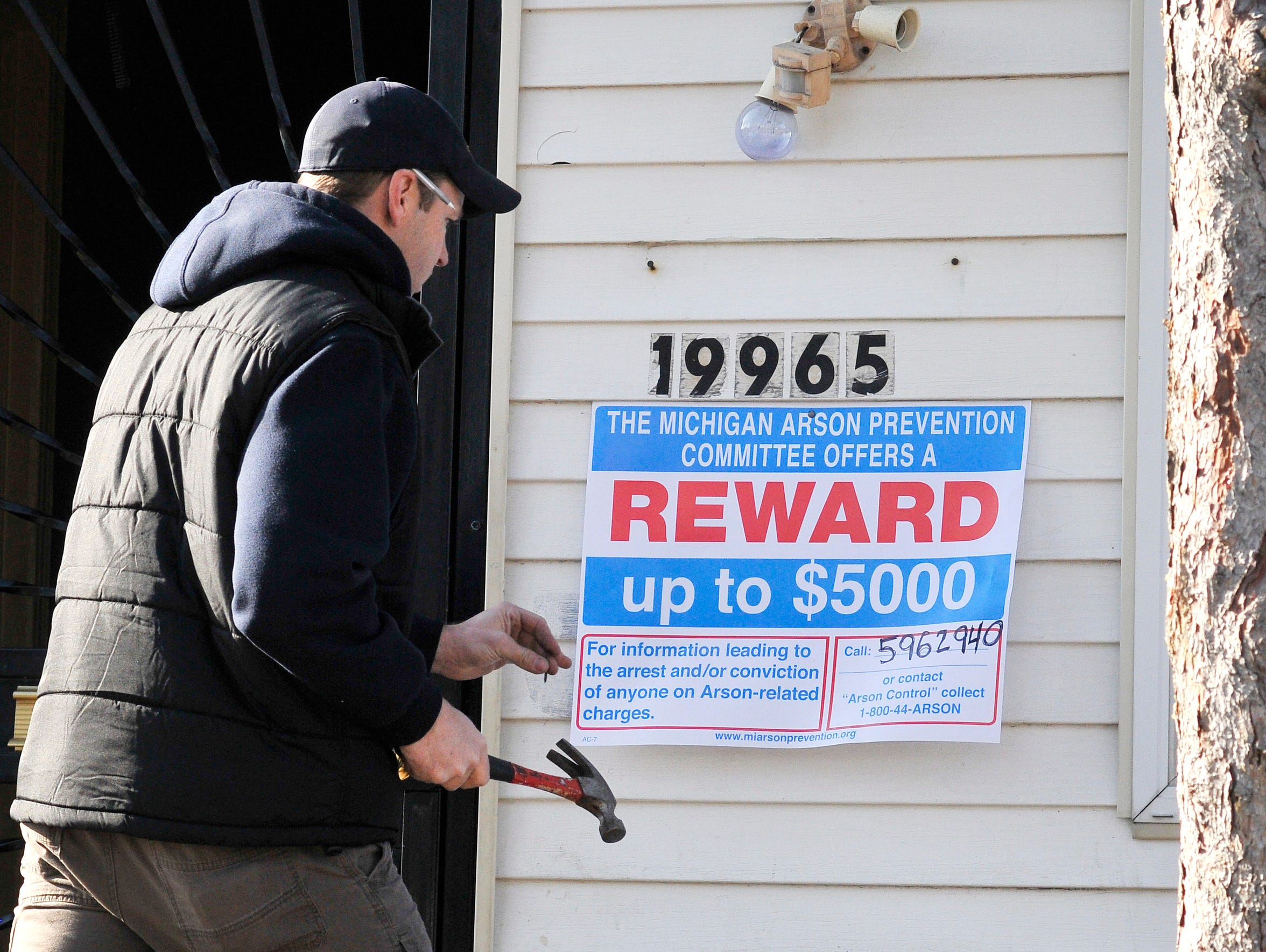 Arson investigator Lt. Joe Cron places a reward sign