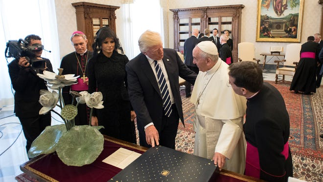 """Pope Francis exchanges gifts with President Donald Trump on the occasion of their private audience at the Vatican on Wednesday. Trump gave the Pope a bronze sculpture of a flowering lotus (far left) by Stuart artist Geoffrey Smith called """"Rising Above"""" representing hope for a peaceful tomorrow, as it evokes two universal values: unity and resilience. Smith is best known on the Treasure Coast for his """"Stuart Sailfish,"""" an 18-foot monument in downtown Stuart that serves as the iconic symbol of the city."""