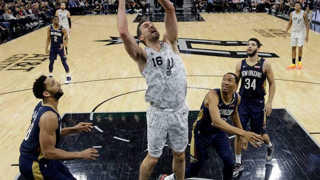 From Saturday, Feb. 2, 2019, San Antonio Spurs center Pau Gasol (16) shoots past New Orleans Pelicans center Jahlil Okafor (8), forward Wesley Johnson (33) and guard Kenrich Williams (34) during the second half of an NBA basketball game in San Antonio. Pau Gasol wants to return to the NBA but does not rule out going back to Europe for his retirement.