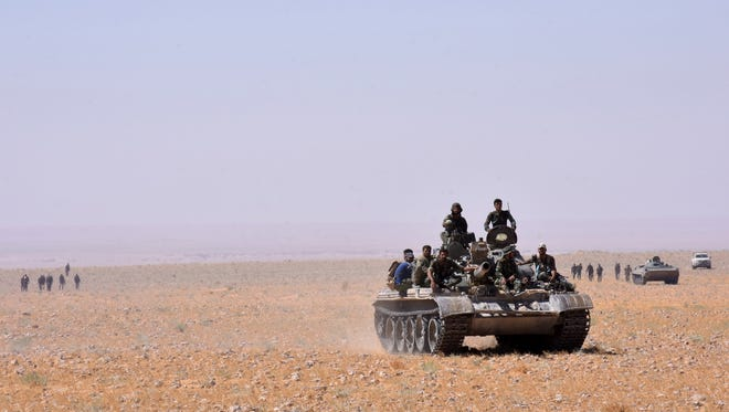 Syria government forces advance in Al-Shula on the southwestern outskirts of Deir Ezzor, on Sept. 7, 2017, during the ongoing battle against the Islamic State.