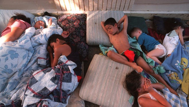 Children from two famlies in New York City sleep on the sidewalk in front of their building on West 188th St. to escape the heat during a power failure on July 7, 1999. Hotter nighttime temperatures appear to be disrupting our sleep patterns, a new study finds.