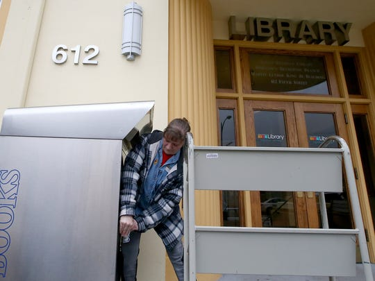 Library assistant Kathy Marshall locks up the book return box after emptying it Tuesday in front of the downtown Bremerton branch.