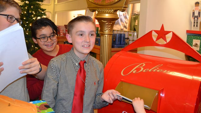 "Eighth-grader AJ Silvestri of Old Bridge deposits the first of more than 78,000 in the ""BELIEVE"" mailbox, located inside Macy's at the Brunswick Square Mall in East Brunswick."