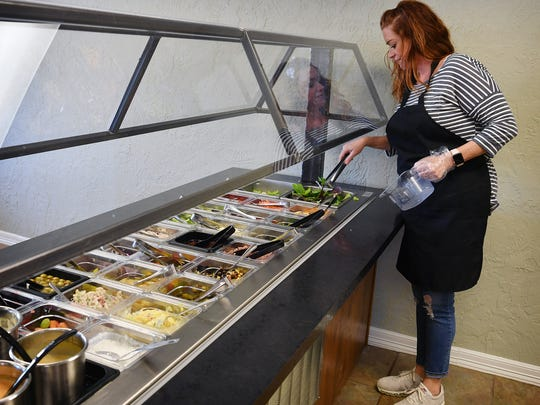 Sally Harlow, owner of Doorway To Gourmet in Iowa Park, refills items on the salad bar. The new restaurant offers breakfast, lunch and dinner, has a bakery on site and caters events and parties.