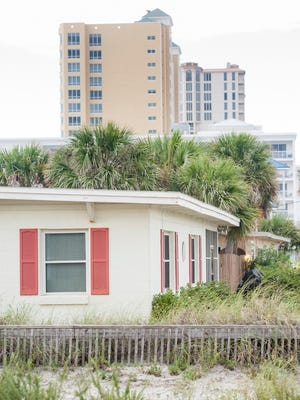 High-rise buildings in the distance dwarf the simple cement block homes that were built in the mid-1900's on Pensacola Beach.  Wednesday, August 17, 2016.