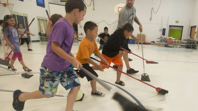 Colorado Eagles defenseman Sean Zimmerman plays a game of broom stick hockey with a BASE Camp class at O'Dea Elementary School in this June 19 file photo.