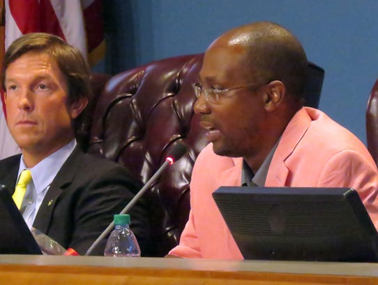 Escambia County Commissioner Lumon May, right, talks during a commissioners meeting in June 2014.