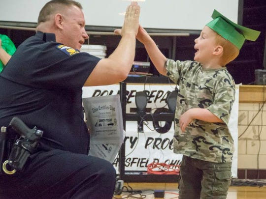 Terrance Marble, 5, gives Mansfield police Chief Ken Coontz a high-five as he receives his diploma for completing Safety Town in 2014.
