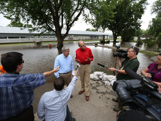 Iowa governor Terry Branstad and HSEMD Director Mark Schouten visit with visit with the media as flood waters of the Rock River stand in the background seen here on Wednesday, June 18, 2014, in Rock Rapids, Iowa.