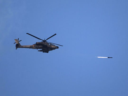 An Israeli Apache attack helicopter shoots a missile over the Gaza Strip as seen from Israel's border with Gaza, on July 18, 2014. The death toll in Gaza hit 265 today as Israel pressed a ground offensive on the 11th day of an assault aimed at stamping out rocket fire, medics said.