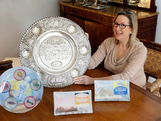 Artist Rachel Heisler Sheinfeld is photographed with two of the Seder plates that she uses for Passover, the larger one that belonged to her husband's parents and one that she made, March 14, 2014 in her Scarsdale home. She decoupaged the Seder plate along with the matzo plates.