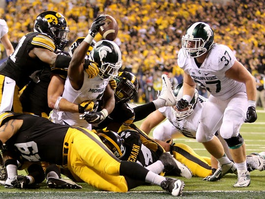Michigan State running back LJ Scott dives in for a touchdown during the fourth quarter against Iowa in the Big Ten Championship at Lucas Oil Stadium in Indianapolis on Saturday, Dec. 5, 2015. The Spartans won, 16-13.
