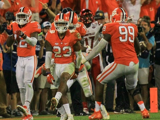 Clemson safety Van Smith (23) celebrates after Marcus Edmond stopped Louisville wide receiver James Quick(17) short of a first down during the fourth quarter on Saturday, Oct. 1, at Memorial Stadium in Clemson.