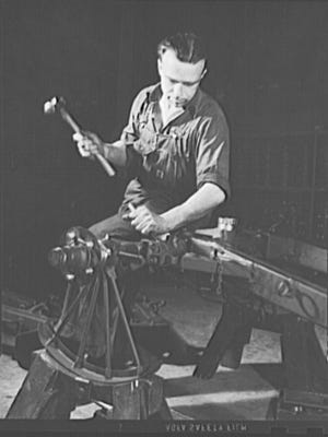 """Shortly after the attack on Pearl Harbor, an Office of War Information photographer visited York Safe and Lock. The photographer wrote: """"This man and the factory he works in were both accustomed to a different kind of work in times of peace. A former silk weaver and loom repairman, this worker now assembles thirty-seven-millimeter gun mounts in a plant which made safe and locks before Pearl Harbor."""""""